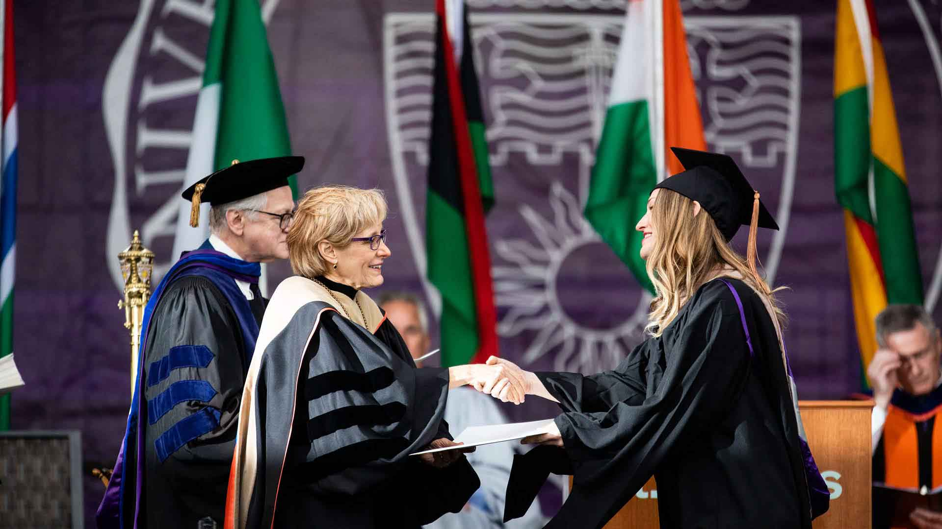 A student shakes hands with President Julie Sullivan as she receives her degree during a commencement ceremony.