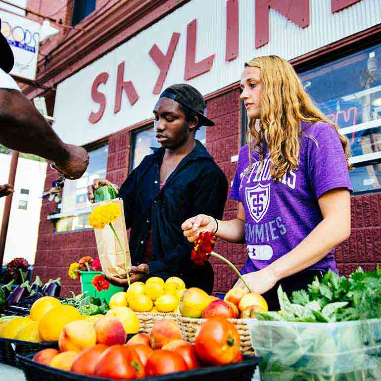 St. Thomas student Nicole Herrli and high school student Steven Fuller operate a Brightside Produce stand in the Phillips neighborhood of Minneapolis.