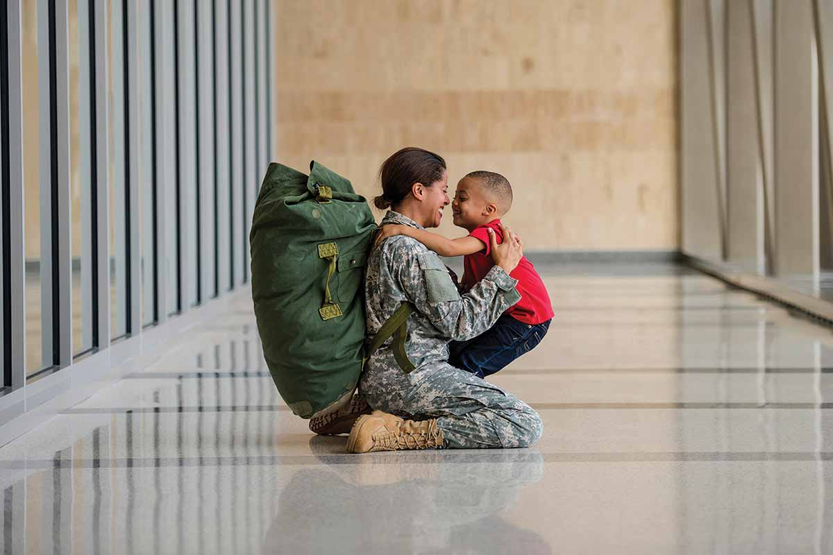 Female dressed in fatigues kneels on ground to greet child.