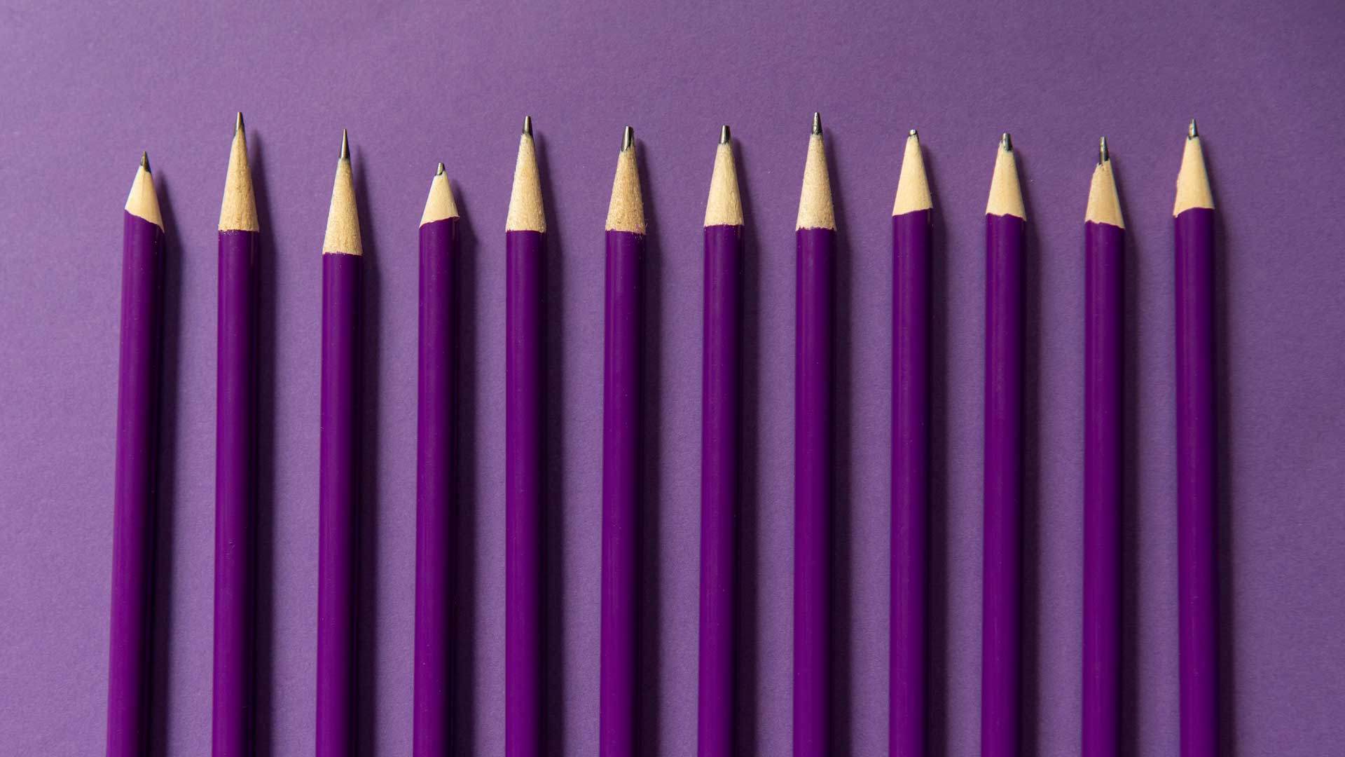 Purple pencils lined up evenly over a purple backdrop.