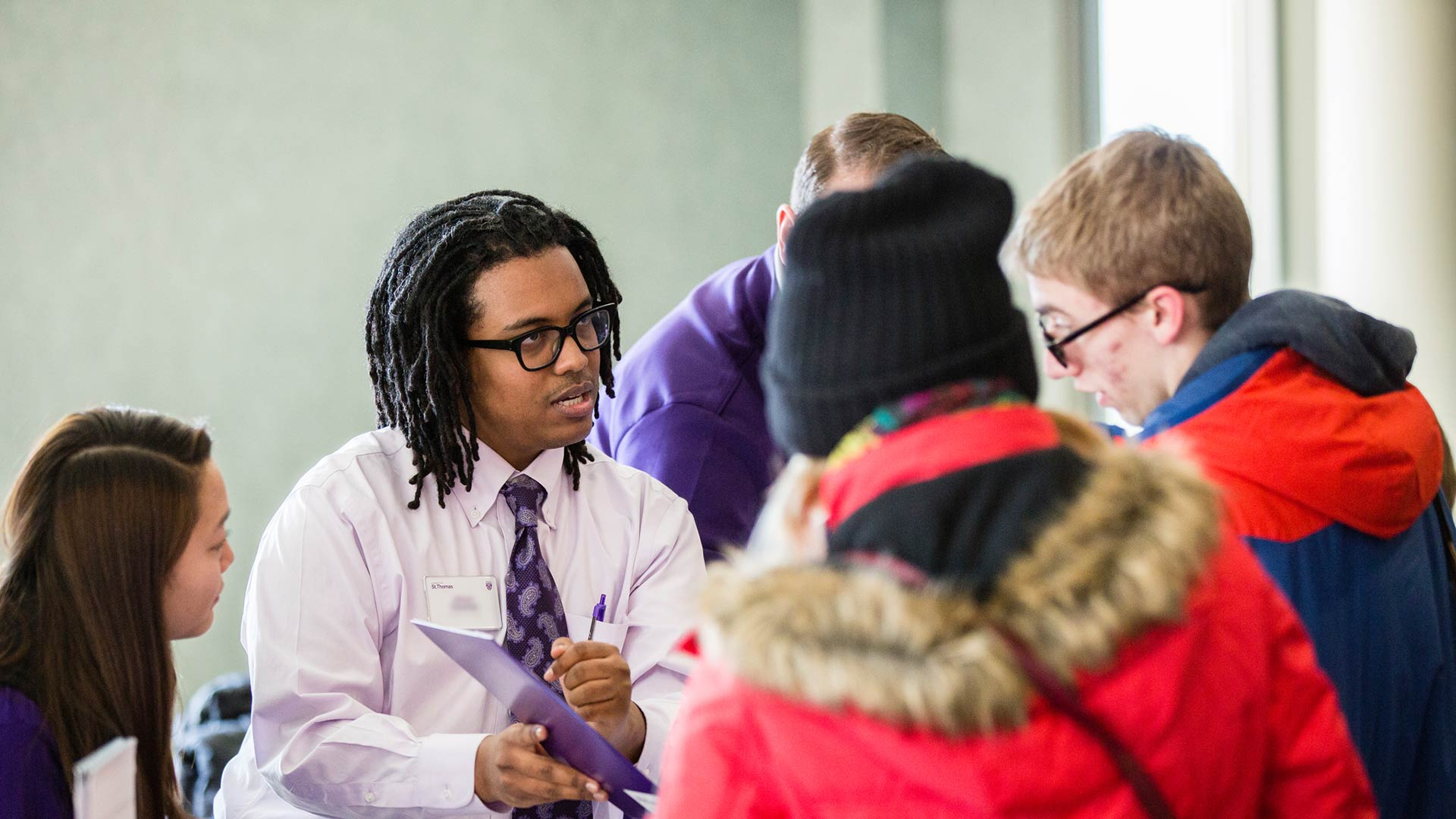 Admissions Counselor Abeye Cherinet (second person on the left) helps prospective students check in during the kickoff of the Tommie Overnight event.