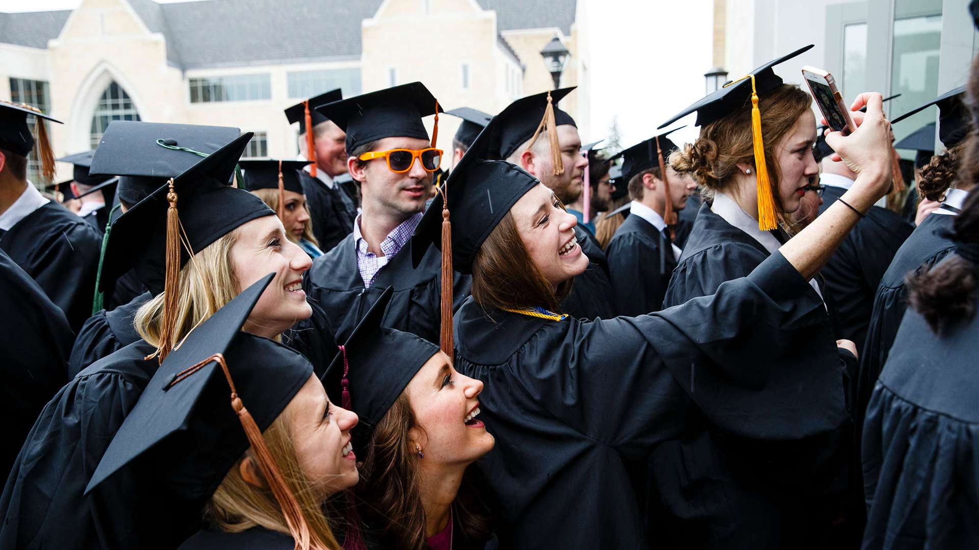 Seniors take a selfie together at an Undergraduate Commencement ceremony