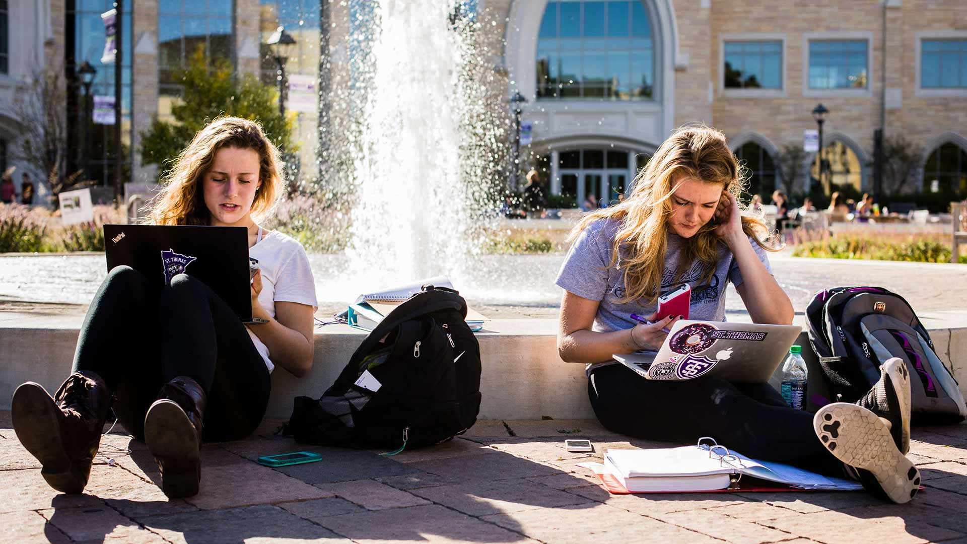 Students work on laptops beside Harpole Fountain.