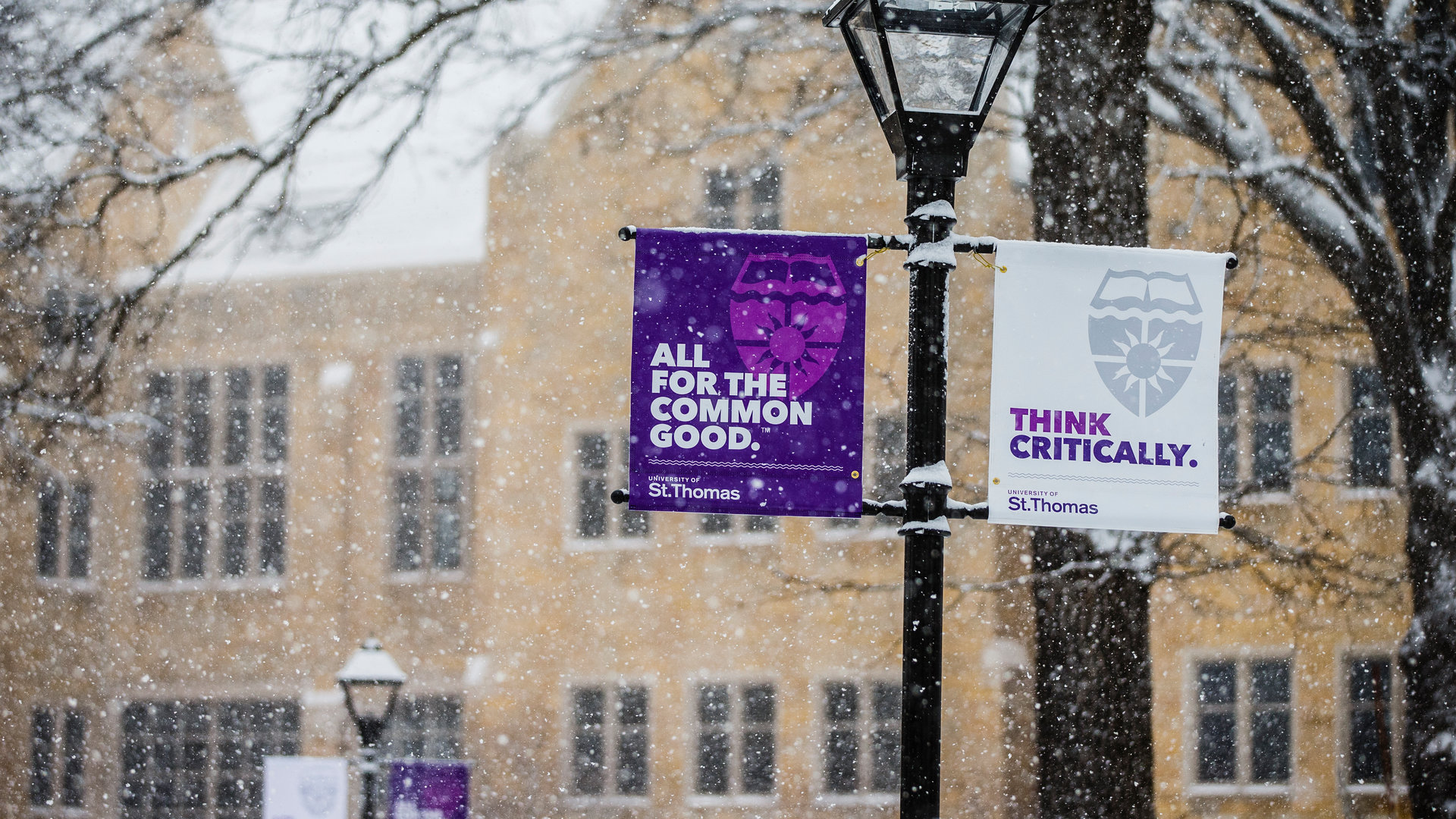 "Two University of St. Thomas branded banners, the one on the left reads ""All for the common good."" The other banner has writing on it that says, ""Think Critically."""