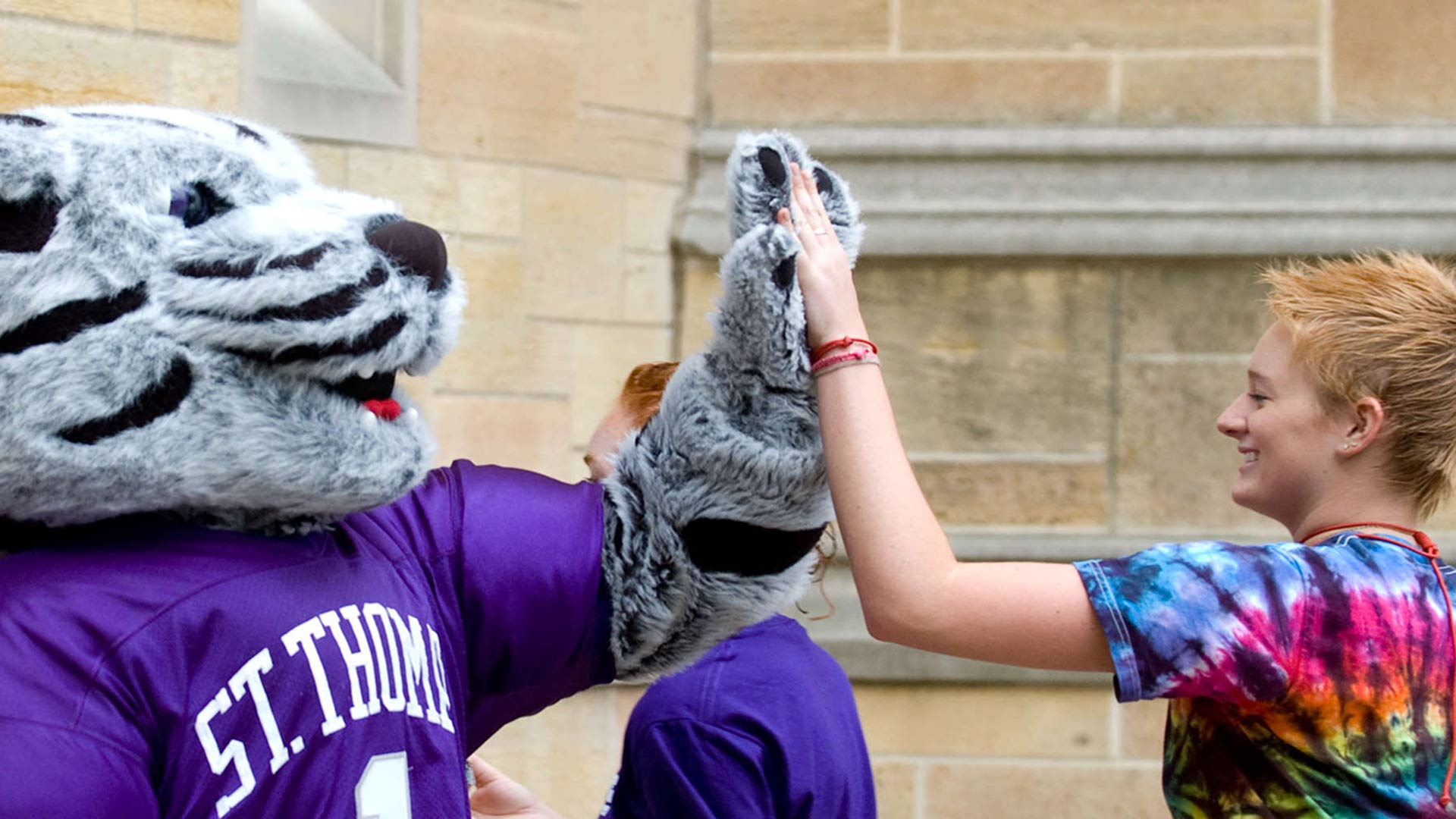 Mascot Tommie gives high five to new student.