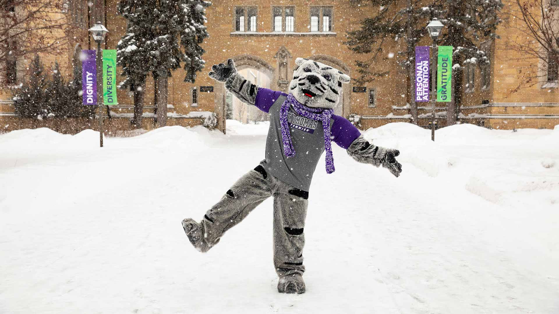 Tommie the mascot walks through the snow in front of The Arches.