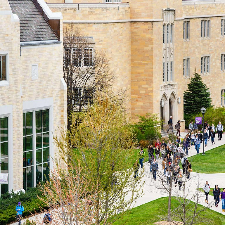 Students enter lower quad from Murray-Herrick Center on a spring day.