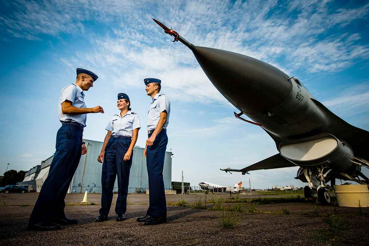 Air Force ROTC cadets talk in front of a F-16 Fighting Falcon jet.