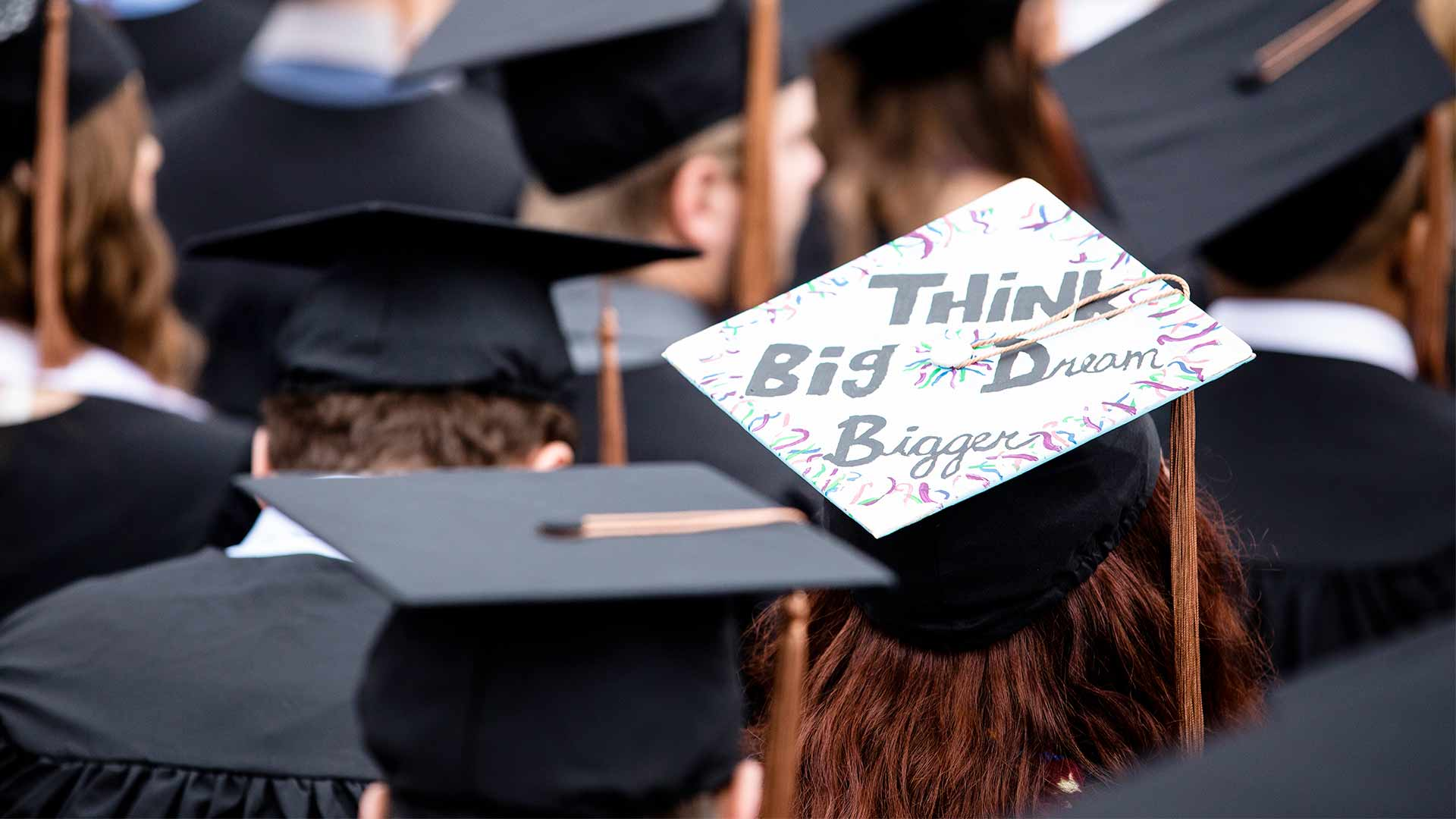 "A student wears a graduation cap that has the words, ""Think Big, Dream Bigger,"" written on it."