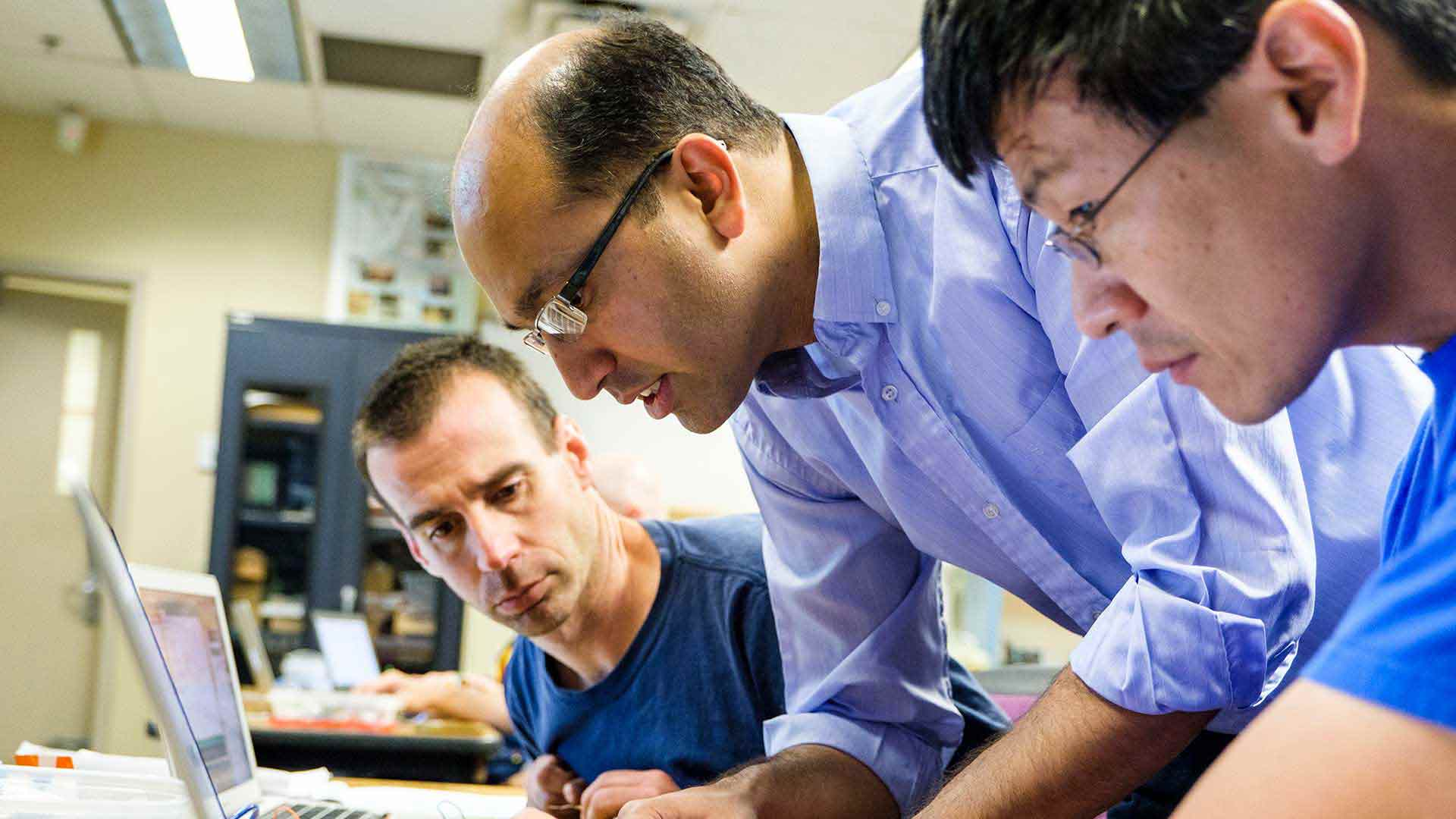 A University of St. Thomas engineering professor assists two students with some work.