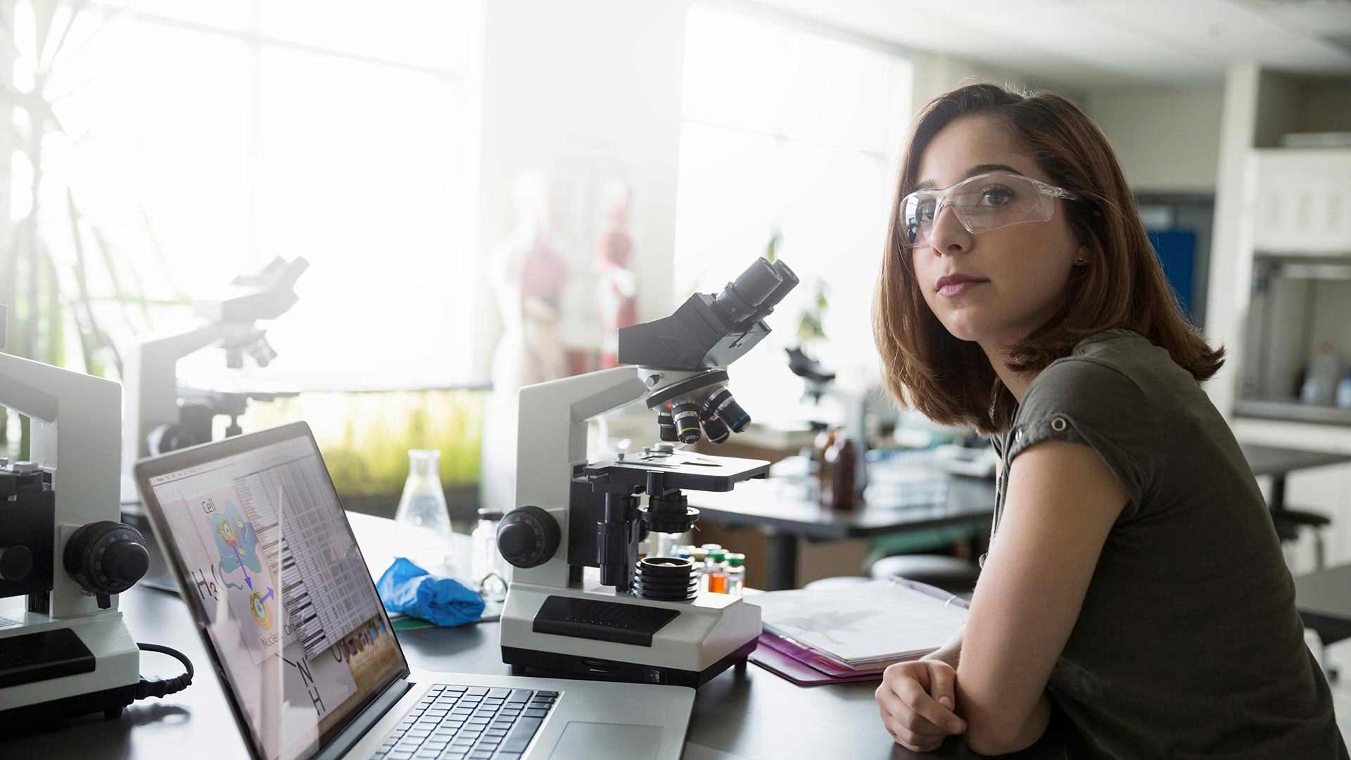 A woman works with a microscope and laptop.