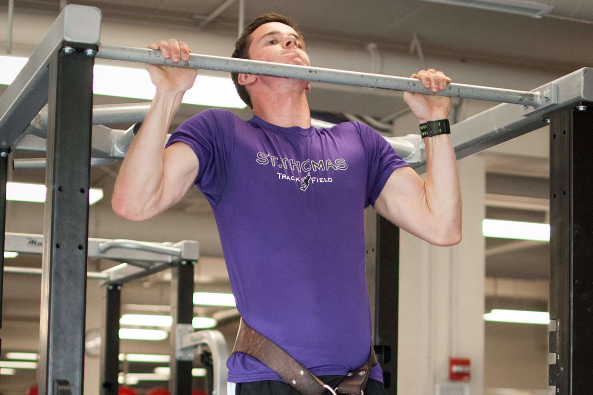 A University of St. Thomas student works out in the weight room.