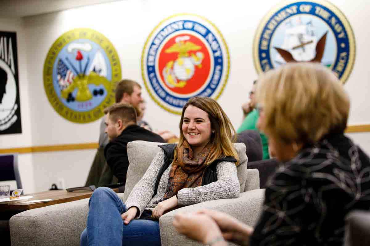 Younger student is smiling while in the Veterans Resource Center on campus.