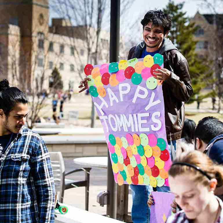 "Students from the """"Happy Tommies"""" group hold a sign"