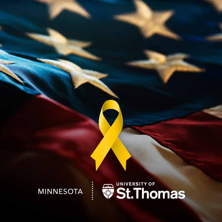 A yellow ribbon lies in front of the American Flag and the St. Thomas logo is at the bottom.